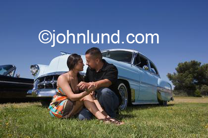 Romantic Hispanic couple sitting on the grass in front of their car.  The car is a classic vintage powder blue car.